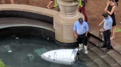 Sad robot takes dip in a fountain